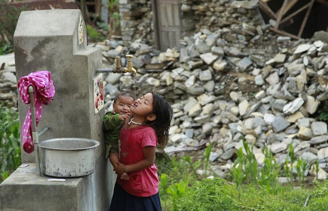 A young girl holding a baby takes a cool drink from a water spigot in the destroyed village of Balua, near the epicenter of Saturday's massive earthquake, in the Gorkha District of Nepal, Thursday, April 30, 2015. (Photo by Wally Santana/AP Photo)