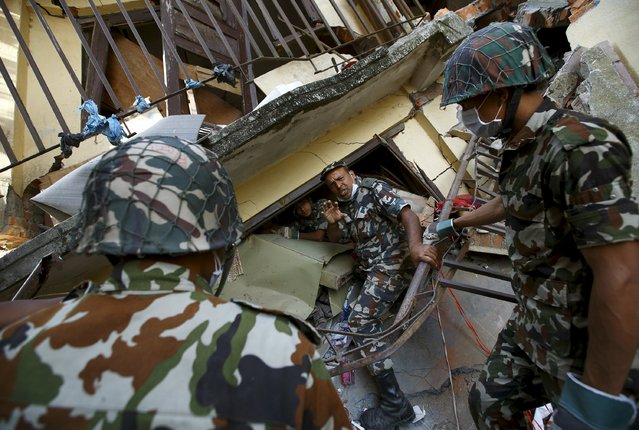Nepalese army personnel help to recover belongings from a collapsed house after the April 25 earthquake at Sankhu, on the outskirts of Kathmandu May 6, 2015. (Photo by Navesh Chitrakar/Reuters)