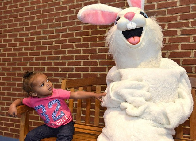 "Amaria Ferguson, 2, tickles the Easter Bunny on Saturday, March 19, 2016, during the YWCA ""Eggstravaganza"" in Bristol, Tenn. Breakfast was provided to about 200 people who also took part in face painting, cake walk, t-shirt painting and many more games. (Photo by Earl Neikirk/Bristol Herald Courier via AP Photo)"
