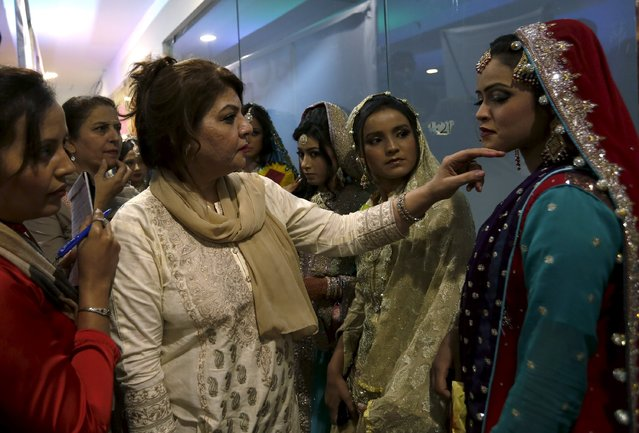 Judges inspect models and their makeup during a self grooming bridal beauty workshop at a local mall in Karachi, Pakistan, March 22, 2016. (Photo by Akhtar Soomro/Reuters)