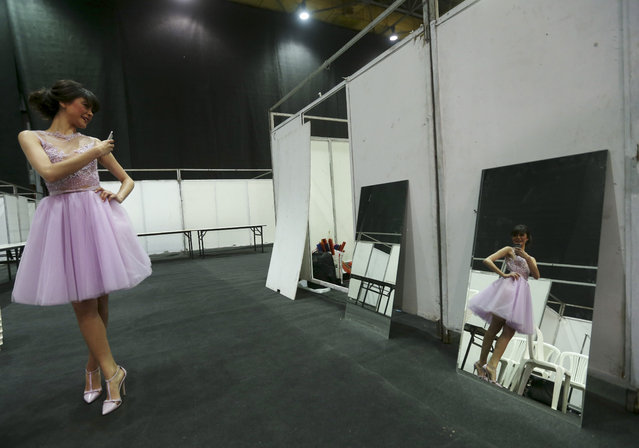 A model takes a picture of herself in the backstage as she prepares to display creations by Lebanese international designer Abed Mahfouz during his Spring-Summer 2015 fashion show in Beirut, Lebanon, Wednesday, April 29, 2015. (Photo by Hussein Malla/AP Photo)