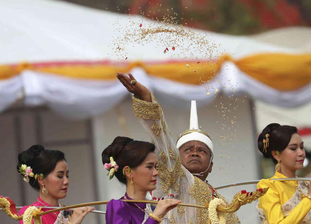 The leader of the plowing ceremony Anan Suwannart throws rice seeds into the field during the royal event in Bangkok, Thailand, Thursday, May 9, 2019. The annual event marks the beginning of the growing season in Thailand for rice. (Photo by Sakchai Lalit/AP Photo)
