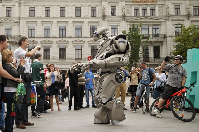 People watch Titan the Robot performing in Bucharest, Romania, Monday, May 11, 2015s. (Photo by Vadim Ghirda/AP Photo)