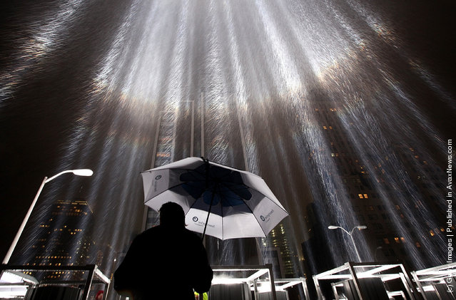 A worker holds an umbrella while adjusting beams of the Tribute in Lights ahead of the tenth anniversary of the September 11 terrorist attacks