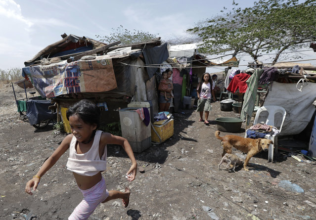 In this Thursday, May 9, 2019, photo, children play outside their shanty at Manila's former dumpsite Smokey Mountain, Philippines. Philippine President Rodrigo Duterte's name is not on the ballot but Monday's mid-term elections are seen as a referendum on his phenomenal rise to power, marked by his gory anti-drug crackdown and his embrace of China. (Photo by Aaron Favila/AP Photo)