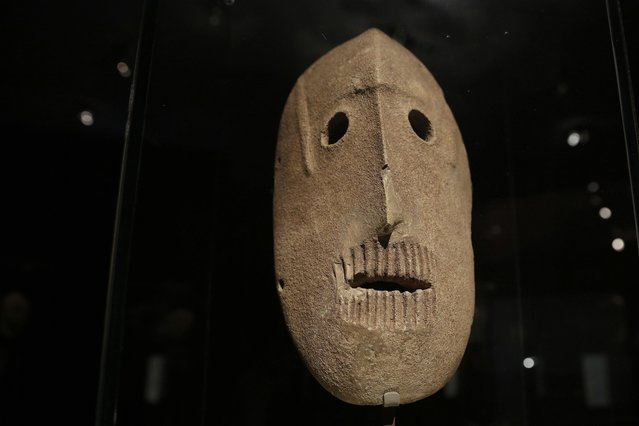 """In this  Monday, March 10, 2014 photo, a 9,000 year-old mask is on display at the Israel Museum in Jerusalem. The exhibition called """"Face To Face"""" shows eleven stone masks, said to have been discovered in the Judean desert and hills near Jerusalem, which date back 9,000 years and offer a rare glimpse at some of civilization's first communal rituals. (Photo by Tsafrir Abayov/AP Photo)"""