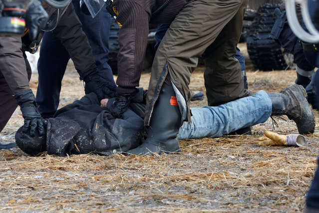 Police detain a protester in the main opposition camp against the Dakota Access oil pipeline near Cannon Ball, North Dakota, U.S., February 23, 2017. (Photo by Terray Sylvester/Reuters)