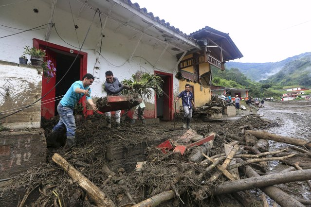 Residents remove debris in front their damaged house, after a landslide close to the municipality of Salgar in Antioquia department, Colombia May 19, 2015. (Photo by Jose Miguel Gomez/Reuters)