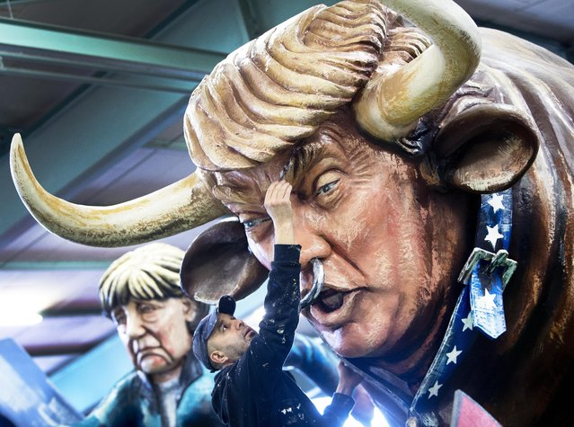 An artist works for media on a figure depicting US President Donald Trump as a bull during a press preview in a hall of the Mainz carnival club in Mainz, Germany,Tuesday, February 26, 2019. Carnival groups and clubs in Germany are putting their final touches on their elaborate floats with outrageous caricatures depicting political themes for this year's parades during Carnival celebrations. (Photo by Michael Probst/AP Photo)