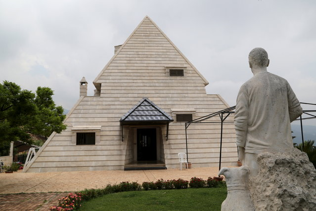A statue is pictured in front of a pyramid house in the village of Miziara, northern Lebanon May 12, 2015. (Photo by Aziz Taher/Reuters)