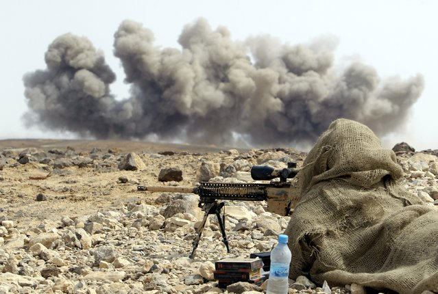 """A solider watches smoke rising as they take part in joint Jordan-US maneuvers during the """"Eager Lion"""" military exercises, in  Mudawwara, near the border with Saudi Arabia, on May 18, 2015. The annual """"Eager Lion"""" exercises includes the participation of 10,000 troops from at least 18 countries, and incorporates scenarios including disaster relief and air defense. (Photo by Khalil Mazraawi/AFP Photo)"""