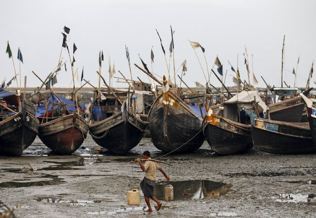 A Rohingya Muslim man carries containers of water in front of boats near a jetty at a refugee camp outside Sittwe, Myanmar May 21, 2015. Scores of Myanmar's minority Rohingya Muslims are paying off people smugglers and returning to the squalid camps they used to live in after being held for months on overcrowded ships that were to take them to Thailand but did not move far from shore. (Photo by Soe Zeya Tun/Reuters)