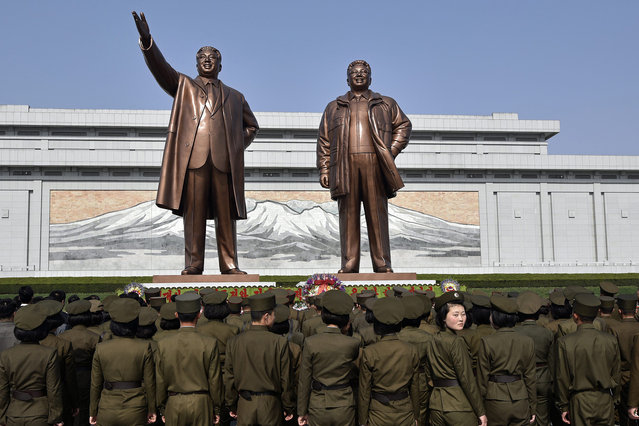 Young military personnel stand in front of large statues of former leaders Kim Il-sung (L) and Kim Jong-il at Mansu Hill in Pyongyang, North Korea, 15 April 2016. (Photo by Franck Robichon/EPA)