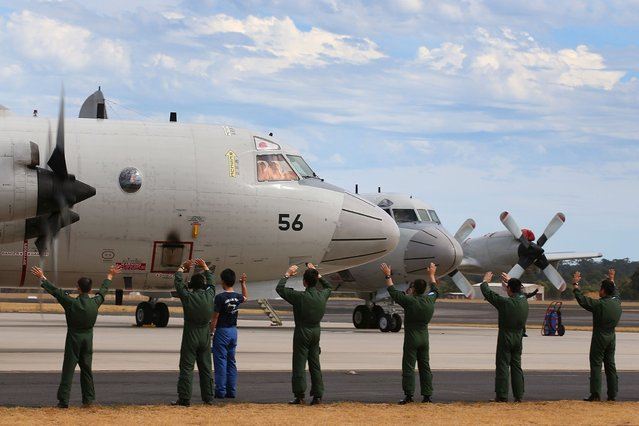 Japanese Maritime Self Defence Force personnel wave farewell to a P-3C Orion as it taxis from the RAAF base Pearce in Bullbrook, 35 kms north of Perth on March 24, 2014 to depart to search for missing Malaysia Airlines flight MH370 over the southern Indian Ocean. Ships and planes from several nations swarmed over the southern Indian Ocean on March 24 as mounting evidence of floating debris energised the search for Malaysia's missing passenger jet. (Photo by Paul Kane /AFP Photo)