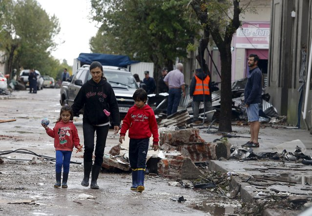 People walk as debris is seen along a street in Dolores, the day after the city was hit by a tornado, April 16, 2016. (Photo by Andres Stapff/Reuters)