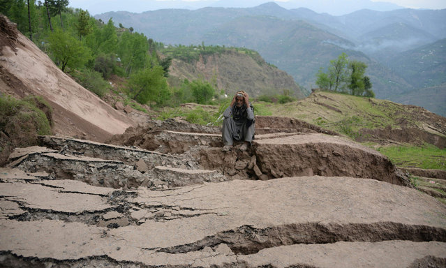 A Pakistani Kashmiri resident sits on cracks land following landslides in Danna village, some 48 kilometers from Muzaffarabad, the capital of Pakistani part of Kashmir on April 16, 2016. Hundreds of people have been shifting to safer places as their houses have been destroyed as large areas started moving downward in the land due to massive landslides. Pakistan last week ended the search for 23 people buried by a landslide in the north, after last week's heavy rains that authorities said killed 117 people. (Photo by Sajjad Qayyum/AFP Photo)