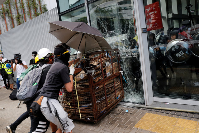 Protesters try to break into the Legislative Council building where riot police are seen, during the anniversary of Hong Kong's handover to China in Hong Kong, China on July 1, 2019. (Photo by Tyrone Siu/Reuters)