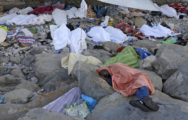Migrants sleep on the rocky beach at the Franco-Italian border near Menton, southeastern France Wednesday, June 17, 2015. European Union nations failed to bridge differences Tuesday over an emergency plan to share the burden of the thousands of refugees crossing the Mediterranean Sea, while on the French-Italian border, police in riot gear forcibly removed dozens of migrants. (AP Photo/Lionel Cironneau)