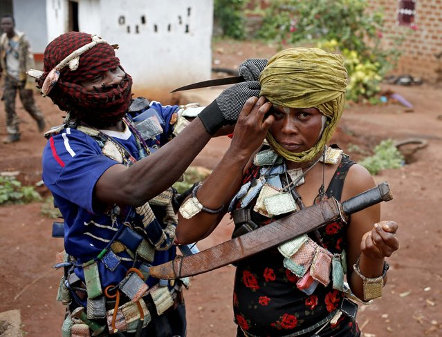 A masked member of the anti-balaka, a Christian militia, adjusts the scarf of his female comrade before they patrol the village of Zawa April 8, 2014. (Photo by Goran Tomasevic/Reuters)