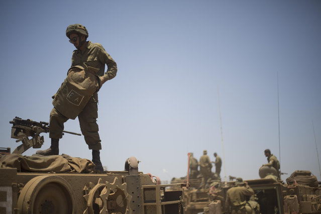 Israeli soldiers stand on top of armored military vehicles during training exercises in the Israeli-occupied Golan Heights, near the border with Syria, Wednesday, June 17, 2015. Syrian rebels launched a wide-ranging offensive against Syrian government positions near the Golan Heights on Wednesday, after tit-for-tat shelling in and around Damascus left at least 33 people dead, activists said. Insurgents have been on the offensive in southern Syria for the past three months, capturing military bases, villages and a border crossing point with Jordan. (AP Photo/Ariel Schalit)