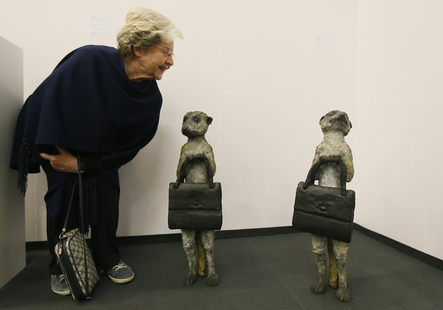 "A woman looks at bronze sculptures ""Meercat 1"" and ""Meercat 2"" by British artist Laura Ford at the ""Art Cologne"" art fair in Cologne April 9, 2014. The sculptures are on sale for 19,000 euros each. Some 200 international exhibitors are taking part in the 48th Art Cologne, one of the world's leading fairs for contemporary art. (Photo by Wolfgang Rattay/Reuters)"
