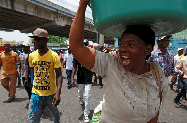 A woman shouts while participating in a march organized by sugar cane workers in Santo Domingo, Dominican Republic, June 25, 2015. Hundreds of Haitian migrants and Dominicans of Haitian descent took to the streets to protest against the risk of deportation from the Dominican Republic. (Photo by Ricardo Rojas/Reuters)