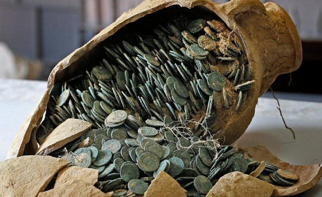 A picture made available on 29 April 2016 shows one of 19 Roman amphoras discovered in the town of Tomares, near Seville, containing around 600 kg of bronze and silver coins dating from the 4th century, in Seville, southern Spain, 28 April 2016. The amphoras, unearthed during excavation works for an electric main close to Zaudin Park in Tomares, are full with coins that are being examined by archeologists from Seville. The coins may have been part of a tax collection or levies paid to the army, according to first theories of experts. (Photo by Jose Manuel Vidal/EPA)