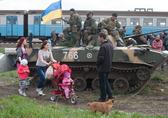 People walk past an Ukrainian Army combat vehicle parked near a railway in Kramatorsk, Ukraine, Wednesday, April 16, 2014. The central government has so far been unable to rein in the insurgents, who it says are being stirred up by paid operatives from Russia and have seized numerous government facilities in at least nine eastern cities to press their demands for broader autonomy and closer ties with Russia. (Photo by Evgeniy Maloletka/AP Photo)