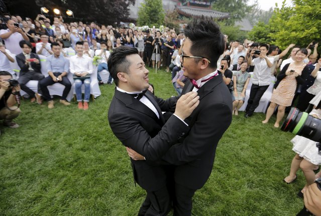 Ling Jueding (L) reacts after kissing his partner Gino during their wedding ceremony at a park in Beijing, June 27, 2015. The gay couple, Ling, 34, and Gino, 27, both internet entrepreneurs in businesses related to China's LGBT community, held their wedding ceremony in Beijing on Saturday after changing the venue for nearly 10 times due to intervention from local police. (Photo by Jason Lee/Reuters)