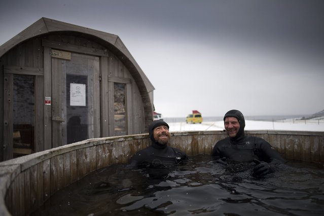 Australian surf legend from the 80' s Tom Carroll, 55, and Norwegian surfer Tommy Olsen keep warm in a hot bath after surfing the Arctic waves of the Atlantic Ocean for the first time in his life on March 9, 2017. (Photo by Olivier Morin/AFP Photo)