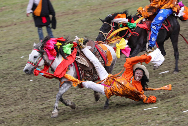 A rider performs horsemanship during a horse racing festival in Litang County, southwest China's Sichuan Province, July 30, 2019. (Photo by Jiang Hongjing/Xinhua News Agency/Alamy Live News)