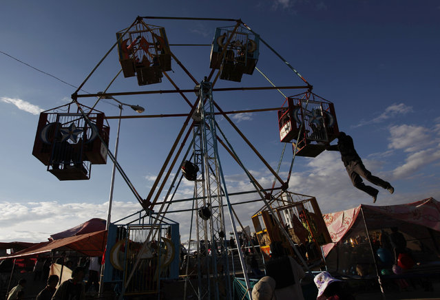 "A youth hangs from a Ferris wheel during the ""Feria de Ramo"", or Palm Fair in El Alto, Bolivia, Saturday, April 12, 2014. The annual three day livestock fair takes place every Palm Sunday weekend and is a Holy Week, or Easter tradition. (Photo by Juan Karita/AP Photo)"