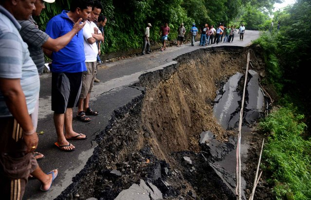 Indian bystanders walk on a landslide affected roadway in the village of Gayabari some 23 kms from Siliguri on July 2, 2015, after landslides struck the eastern state of West Bengal. Landslides triggered by heavy rain killed at least 30 people across India's famed tea-growing region of Darjeeling, with more feared trapped under mounds of mud and debris, police said. (Photo by Diptendu Dutta/AFP Photo)