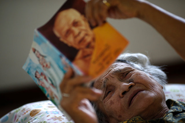 An elderly woman reads a Dhamma book during a physical therapy session at Bangkhae Home Foundation in Bangkok, Thailand, April 27, 2016. (Photo by Athit Perawongmetha/Reuters)