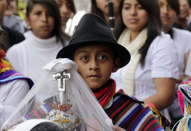 In this June 4, 2015 photo, a boy representing a steward or prioste, carrying a staff or guion, takes part in a Corpus Christi festival, in Pujili, Ecuador. (Photo by Dolores Ochoa/AP Photo)