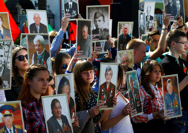 People carry pictures of World War Two participants as they take part in the Memory march during the Victory Day celebrations, marking the 71st anniversary of the victory over Nazi Germany in World War Two, in the town of Dyatlovo, Belarus May 9, 2016. (Photo by Vasily Fedosenko/Reuters)