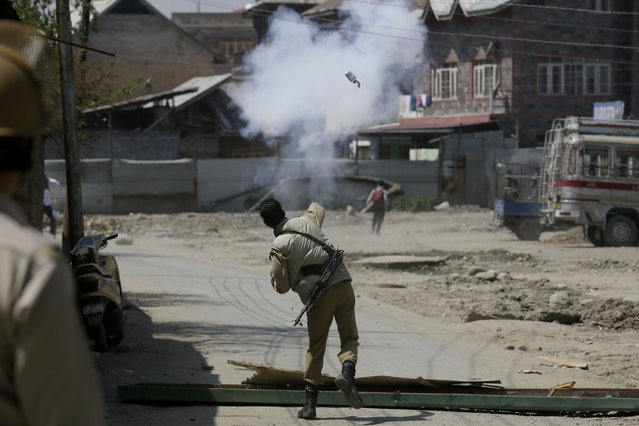 An Indian policeman throws tear smoke shell on protesting Kashmiri students as they clash in Srinagar, Indian controlled Kashmir, Monday, April 17, 2017. (Photo by Mukhtar Khan/AP Photo)