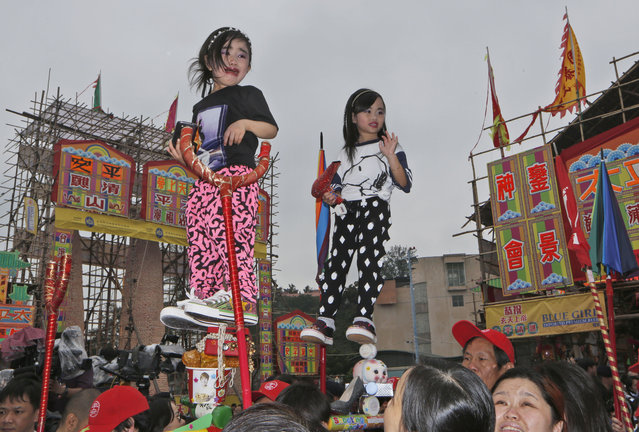 A young performer cries as she parades during the Bun Festival on Cheung Chau island in Hong Kong Tuesday, May 6, 2014. Bun Festival, the Taoist God of the Sea, is worshipped and evil spirits are believed to be scared away by loud gongs and drums during the procession. The celebration includes bun scrambling, parades, opera performances, and children dressed in colorful costumes. (Photo by Kin Cheung/AP Photo)