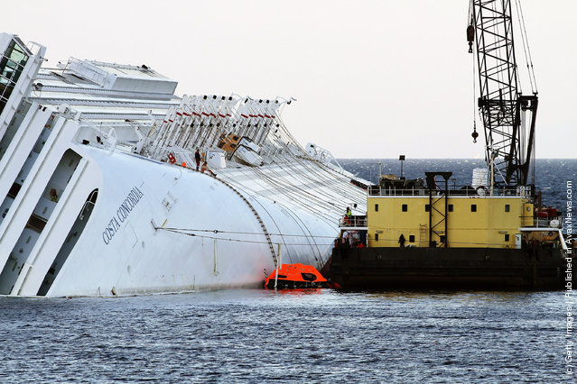 Rotterdam based SMIT and Livorno based NERI salvage workers start their work of diesel recovery on a pontoon from the the cruise ship Costa Concordia that lies stricken off the shore of the island of Giglio