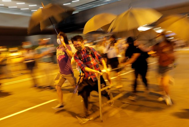 Anti-government protesters run carrying barriers as they block a street in Central Hong Kong, October 4, 2019. (Photo by Susana Vera/Reuters)