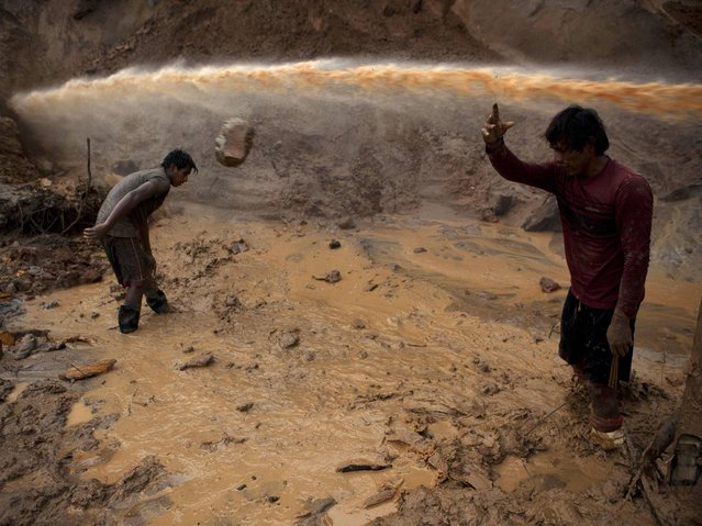 """A jet stream of water passes above two miners known as """"Maraqueros"""" who remove stones and chunks of tree trunks that have been released with the aid of a rustic type of hydraulic jet known locally as a """"Chupadera"""", in La Pampa in Peru's Madre de Dios region. The Chupadera aims powerful jet streams of water at earth walls, releasing the soils that hold the sought after flecks of gold. (Photo by Rodrigo Abd/AP Photo)"""
