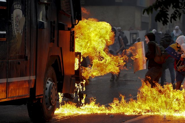 An anti-government protester wearing a Guy Fawkes mask stands with a shield near flames from molotov cocktails thrown at a water cannon by anti-government protesters during riots in Caracas in this April 20, 2014 file photo. (Photo by Jorge Silva/Reuters)