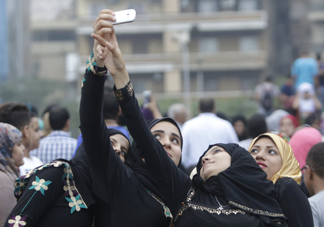 Egyptian girls smile and cheer as they take a selfi with their mobile phone celebrating Eid al-Fitr marking the end of the Muslim holy month of Ramadan in Cairo, Egypt, Friday, July 17, 2015. (Photo by Amr Nabil/AP Photo)