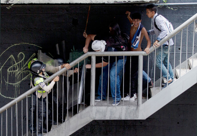 Anti-government demonstrators fight with Bolivarian National police on a pedestrian bridge during an anti-government march toward the headquarters of the national electoral body, CNE, in Caracas, Venezuela, Wednesday, May 18, 2016. (Photo by Fernando Llano/AP Photo)