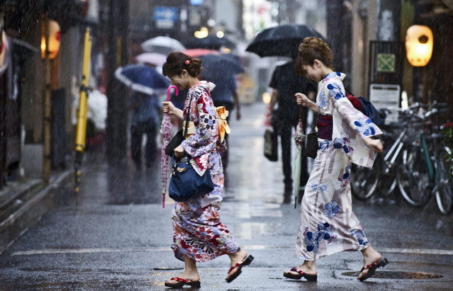 Japanese women wearing kimono walk in the approaching rains of Typhoon Nangka in downtown Kyoto, Japan, 16 July 2015. (Photo by Everett Kennedy Brown/EPA)