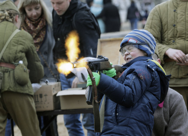 A boy shoots a World War II-era machine gun armed with blanks at a weapon exhibition during a military show in St. Petersburg, Russia, on Sunday, April 30, 2017. (Photo by Dmitri Lovetsky/AP Photo)