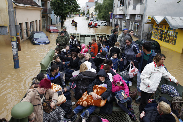 Serbian army soldiers evacuate people in an amphibious vehicle in the flooded town of Obrenovac, southwest of Belgrade, May 17, 2014. Emergency services pulled seven dead bodies from flooded homes in Bosnia on Saturday and soldiers rushed to free hundreds of people stranded in a school in Serbia during the worst floods to hit the Balkans in over a century. (Photo by Marko Djurica/Reuters)