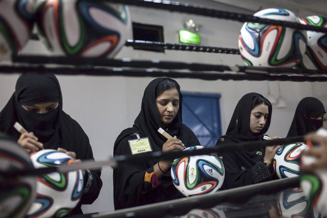 Employees conduct a final check to fix any cavities in the seams of balls inside the soccer ball factory that produces official match balls for the 2014 World Cup in Brazil, in Sialkot, Punjab province May 16, 2014. (Photo by Sara Farid/Reuters)