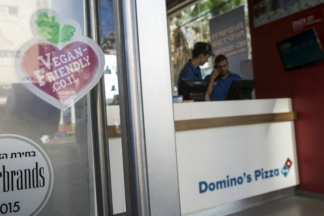 A  vegan friendly sticker in seen on the door of a Domino's Pizza restaurant in Tel Aviv, Israel July 16, 2015. (Photo by Baz Ratner/Reuters)