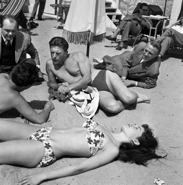 Kirk Douglas on the beach at Cannes with a young actress Brigitte Bardot during the 6th International Cannes Film Festival, 1953. (Photo by SIPA Press/Rex Features/Shutterstock)